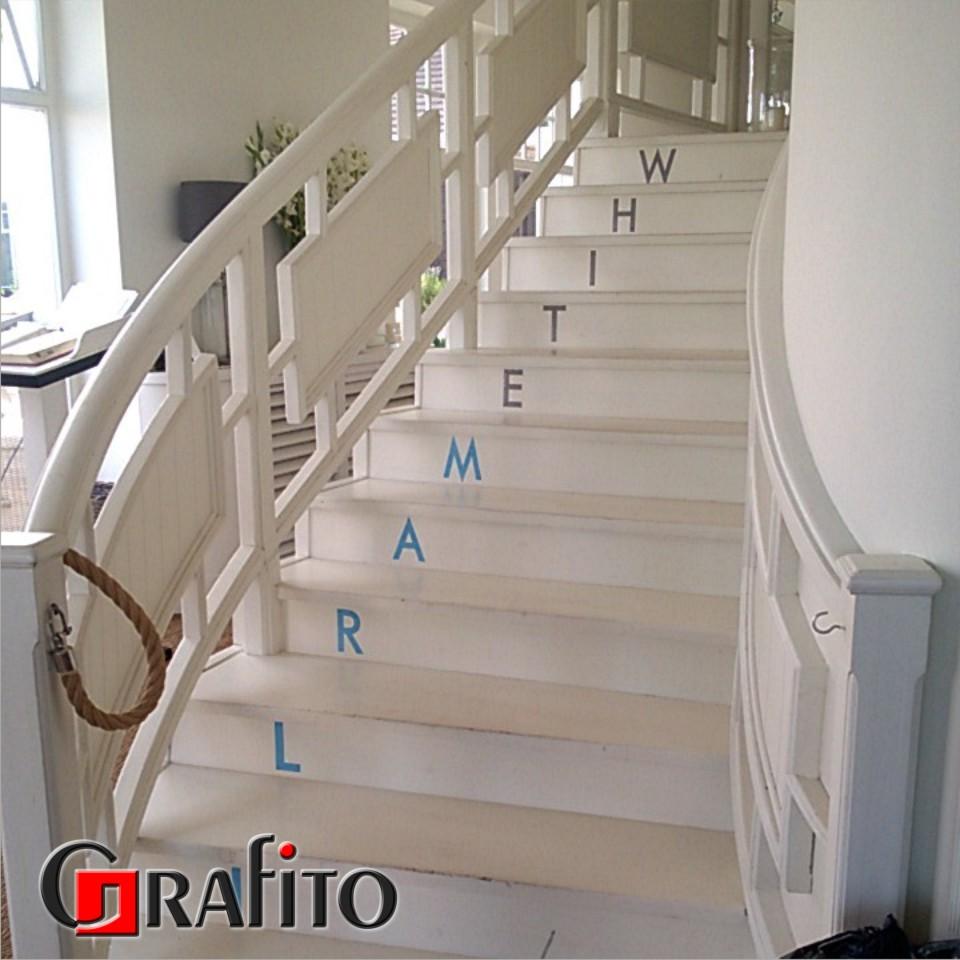 Potykacz - malowane napisy na schodach.